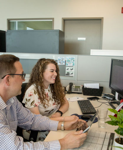 a portrait of smiling woman showing her male coworker a project on her computer
